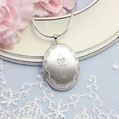 Beautiful silver locket in an oval shape engraved with a Cross. The Cross is set with a genuine diamond.