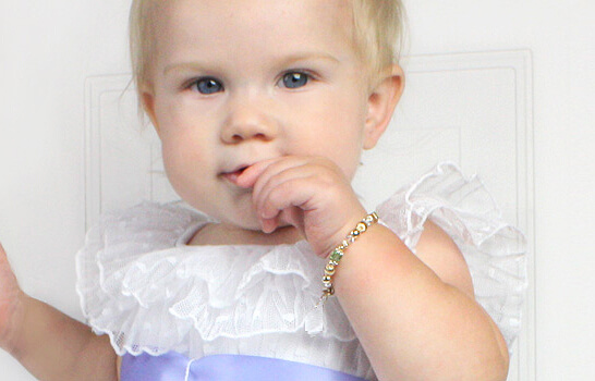 Baby girl wearing gold baby bracelet.