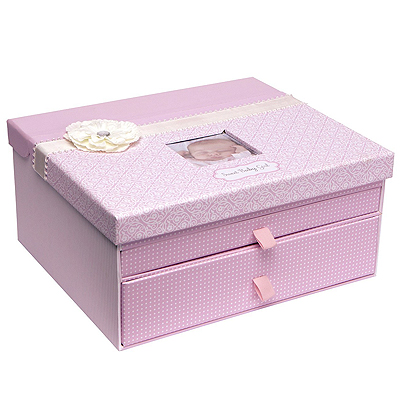 Pink keepsake chest for baby girls with ribbon and flower. Top compartment stores baby book, 2 drawers for other special mementos and photos.