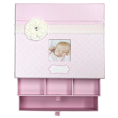 Adorable keepsake chest for baby girls in pearlized pink with ribbon and flower. Top compartment holds memory book, 2 drawers pull out to store other mementos. Baby girl gift.