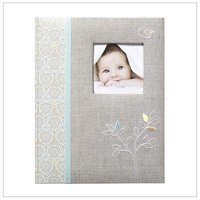Elegant bound baby memory book with padded front, embroidered stitching, customizable picture window, and 68 pages of milestones to record.