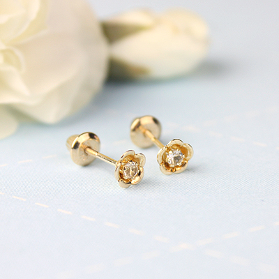 14kt gold April birthstone earrings with a flower shape. Beautiful birthstone earrings for babies and children.