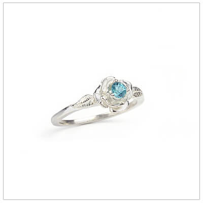 Sterling silver rose-shaped ring set with genuine blue topaz, a silver birthstone ring for December.