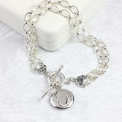 Silver double strand charm bracelet with round locket plus additional charm included.