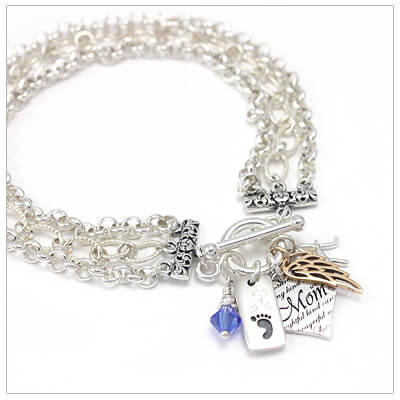 Sterling silver triple chain charm bracelet with included charms.