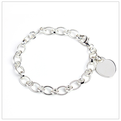Silver oval chain charm bracelet with engraved heart charm.