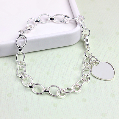 Silver textured oval link charm bracelet for teens and adults with engraved heart charm.