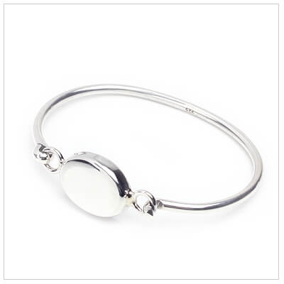 Silver bangle bracelet for children with puffed oval front for engraving.