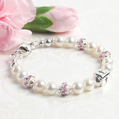 Beautiful baby and infant bracelets in white cultured pearls with sterling silver Cross bead and crystal-set sterling.