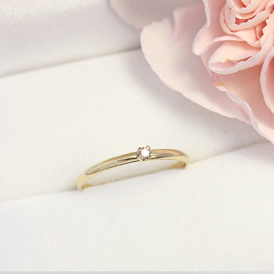 Dainty diamond solitaire ring for girls in 10kt yellow gold.