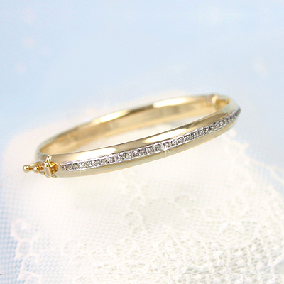 14kt gold bangle bracelets with a full row of diamonds on front. A little luxury! Size 5 inches.