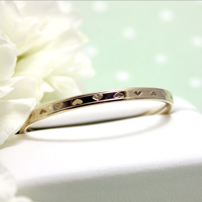 Beautiful gold bangle bracelet for girls with engraved hearts all the way around and a safety clasp.