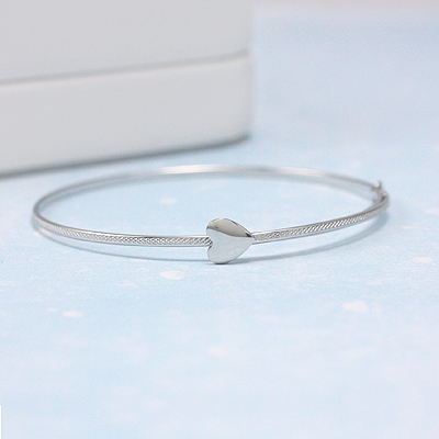 White gold bangle bracelets with textured band and polished heart. Adjusts for baby, toddler & child.