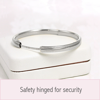 14kt white gold bangle bracelet with a border of hearts all around the bangle. Baby bangles have safety hinge closure.
