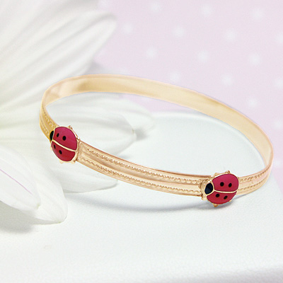 Gold filled bangle bracelet with red ladybugs. Adjustable sizing for baby, toddler, child.
