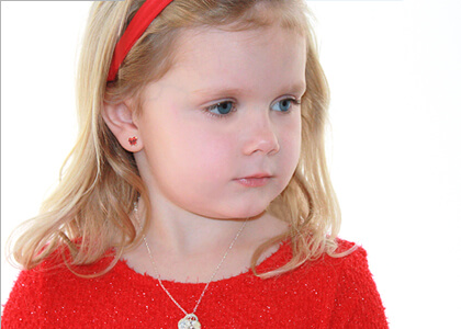 Young girl wearing butterfly shaped birthstone earrings for children.