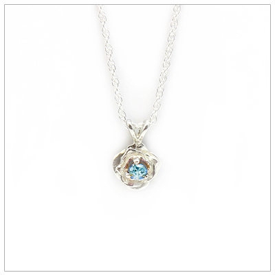 December birthstone necklace in rose shaped sterling silver setting, genuine blue topaz birthstone.