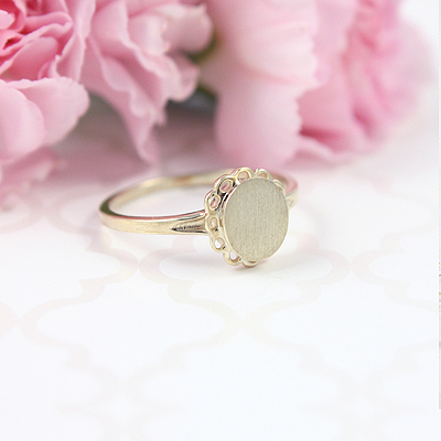 Signet ring for teens in 10kt gold with an oval front and fine looped detailing. Engraving is included on the signet ring.