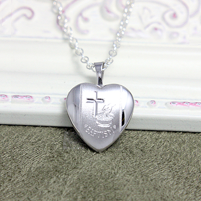 A heart shaped silver locket necklace engraved with a Cross and Baptism symbols. A beautiful silver locket for a special occasion.