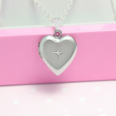 Girls silver heart locket with genuine diamond and chain included. The heart locket holds two photos.