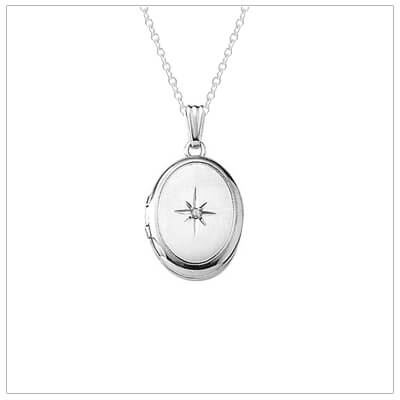 Silver diamond locket necklace for girls in an oval shape. The locket has a matte front and polished back, genuine diamond, and holds two small photos.