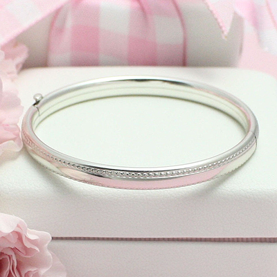 Children's silver bangle bracelet with beaded border and safety clasp.