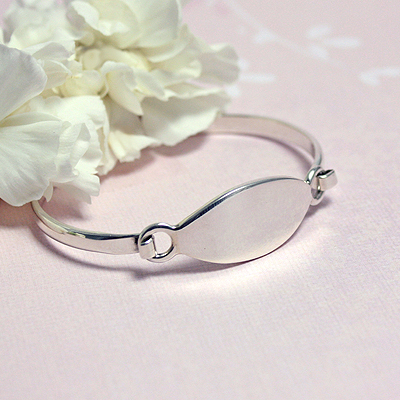 Silver bangle bracelet with a marquise shaped front personalized for kids with custom engraving, engraving included. These bangle bracelets have a front closure.