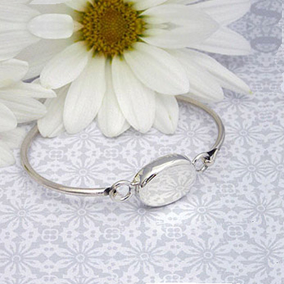 Silver bangle bracelet with oval puffed front personalized with engraving. Child size 6 inches.