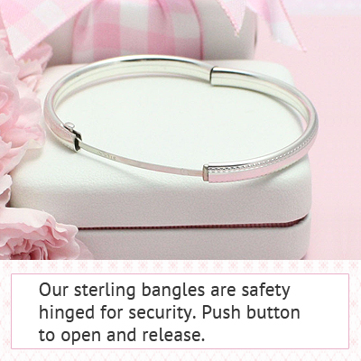 Sterling silver bangle bracelet with an engraved floral pattern and safety clasp for children.