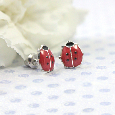 Screw back earrings for babies and children in a red ladybug design. The screw back earrings are sterling silver.