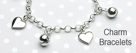 Girls silver charm bracelet with heart and bell charms.