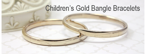 14kt gold bangle bracelets for babies and children with a heart border and safety closure.