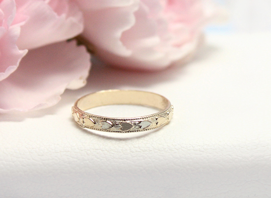 10kt gold baby ring with hearts all around the ring.