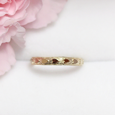 Gold baby ring with hearts around the band; 2 sizes available.