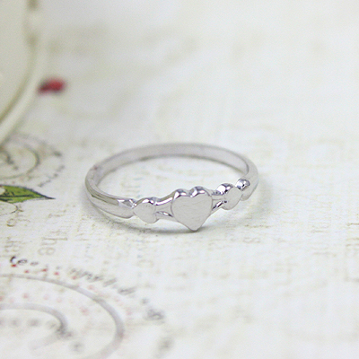 Silver baby ring with three small hearts.