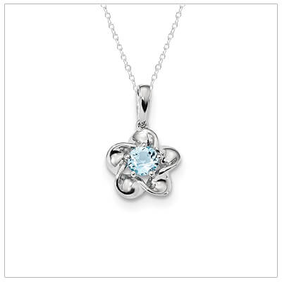 Sterling silver December birthstone necklace with a flower shape and genuine blue topaz.