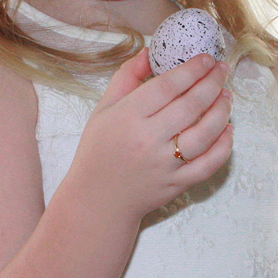 Child wearing gold solitaire-style birthstone ring.