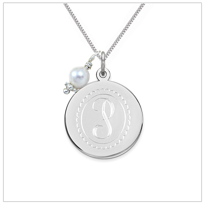 Engraved initial necklace in sterling silver. The engraved necklace includes a pearl charm and sterling silver chain.