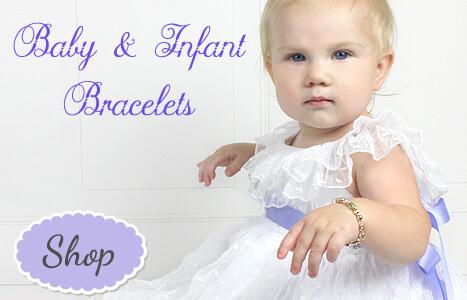 Baby in white dress wearing a gold baby bracelet.