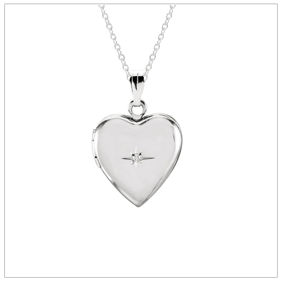 Girls heart shaped locket necklace in bright polished sterling silver with a genuine diamond. Personalize the back of the heart locket with custom engraving.