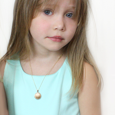 Child wearing girls gold filled embossed round locket. The locket holds two small photos.