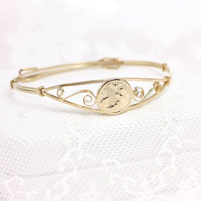 14kt gold filled bangle bracelet with a guardian angel. Adjustable size to fit toddlers and children.