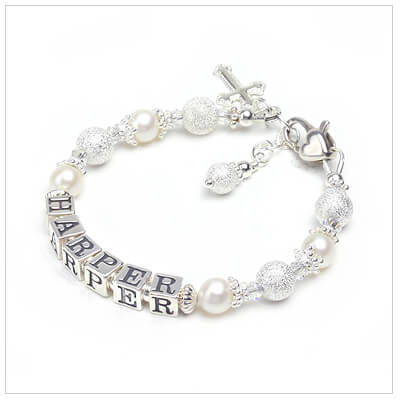 Baby and childrens baptism bracelet in white pearls and shimmery stardust silver beads. Cross charm is included.