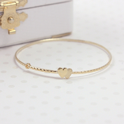 14kt gold bangle bracelets twisted band and two small hearts. Adjustable sizing, 4.75 - 6.25 in.