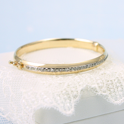 14kt gold bangle bracelets with a full row of diamonds across the front; a lot of sparkle.