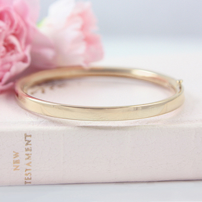 14kt gold bangle bracelet with a bright polished finish and safety clasp, sized for children.