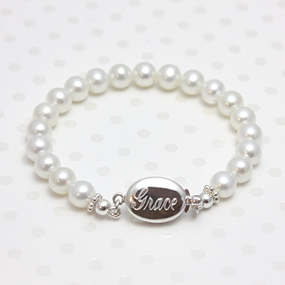 Cultured pearl baby bracelet with custom engraving on the sterling silver safety clasp. Baby's First Pearls bracelet is a customer favorite in fine white pearls.