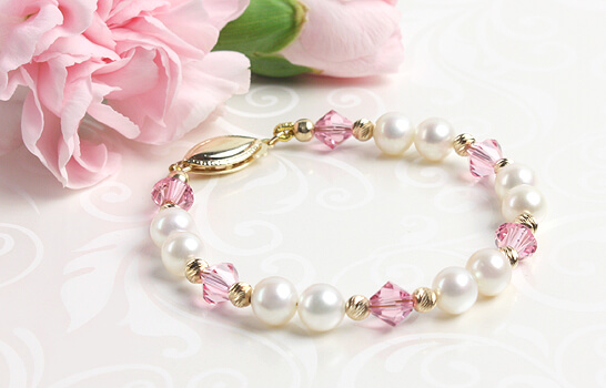 14kt gold baby bracelet with white cultured pearls and soft pink crystals.