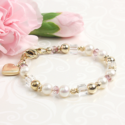 Fine gold baby bracelet with 14kt yellow gold and white cultured pearls. Shown with puffed heart charm.