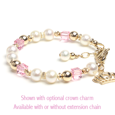 Gold baby and children's bracelet with white cultured pearls and pink cube crystals. Shown with gold crown charm.